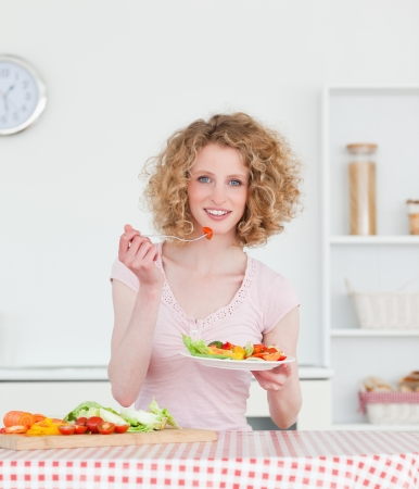 Pretty blonde woman eating some vegetables in the kitchen in her appartment photo