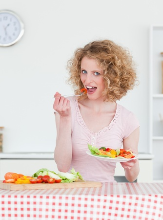 Charming blonde woman eating some vegetables in the kitchen in her appartment photo