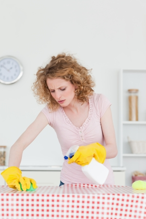 Attractive red-haired woman cleaning a cutting board in the kitchen in her apartment  Stock Photo - 10219198