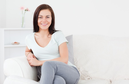 Young woman posing on the sofa in her living room Stock Photo - 10221016