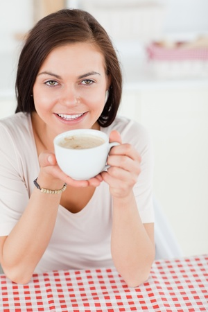 Cute dark-haired woman having a coffee in her kitchen photo