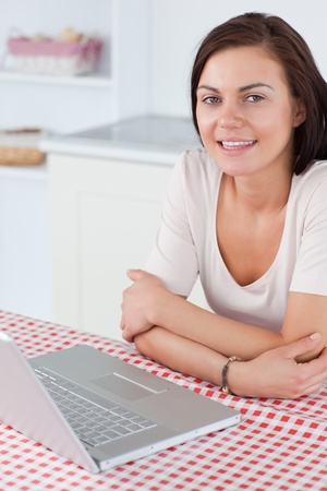 Portrait of a charming woman with a laptop in her kitchen photo