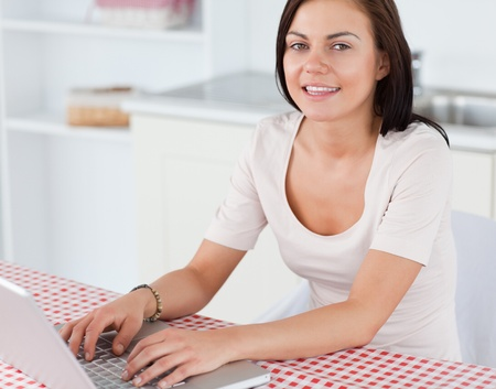 Close up of a smiling woman with a laptop in her kitchen photo