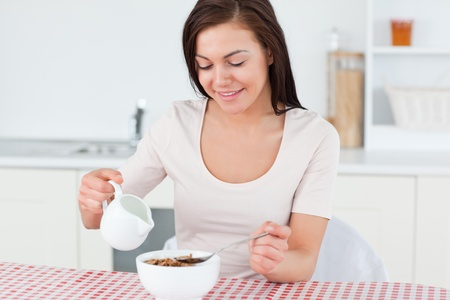 Brunette pouring milk in her cereal in her kitchen photo