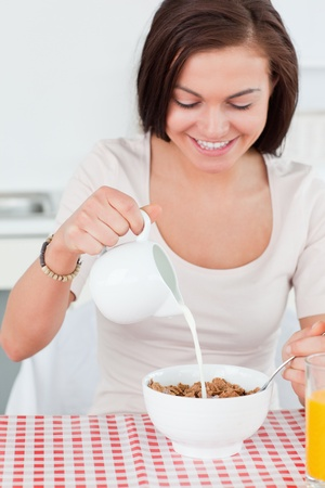 Beautiful dark-haired woman pouring milk in her cereal in her kitchen photo