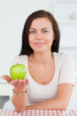 Cute woman showing an apple with the camera focus on the apple photo