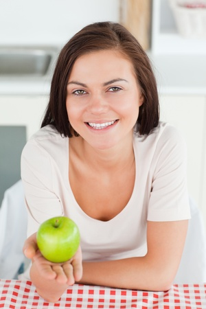 Laughing brunette showing an apple in her kitchen photo