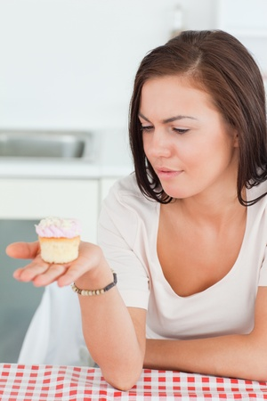Cute brunette looking at a cupcake in her kitchen photo