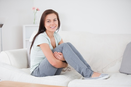 Close up of a young woman posing on her sofa while looking at the camera Stock Photo - 10221140