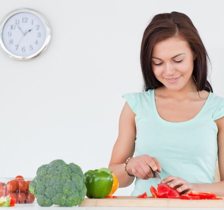 Smiling brunette slicing a pepper in her kitchen Stock Photo - 10220844