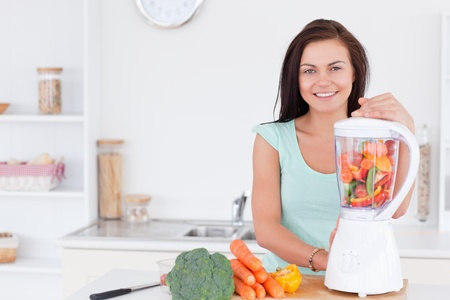 blender: Charming woman using a blender in her kitchen Stock Photo