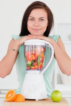 Smiling dark-haired woman posing with a blender in her kitchen photo