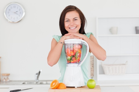 Smiling cute woman posing with a blender while looking at the camera photo