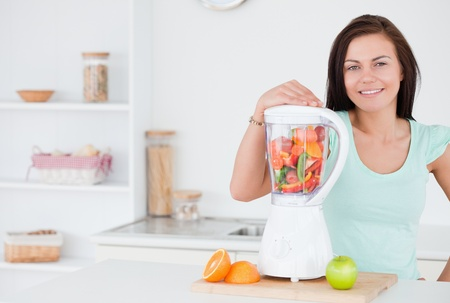 Dark-haired woman posing with a blender photo
