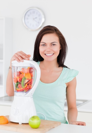 Charming woman posing with a blender in her kitchen photo