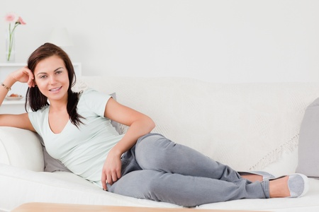 Cute woman lying on her sofa while looking at the camera photo