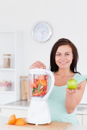 Woman with a blender and an apple while looking at the camera photo