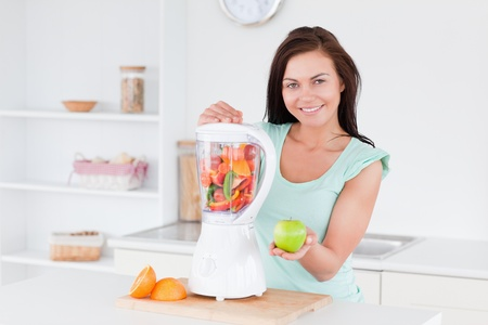 electric mixer: Happy woman with a blender and an apple Stock Photo