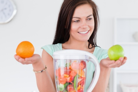 Charming woman with a blender and fruits looking at an apple Stock Photo - 10221155