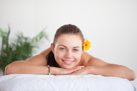 Smiling brunette with a flower on her ear in a spa photo
