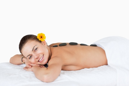 Young woman having a LaStone therapy with a flower on her ear photo