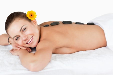 Smiling woman having a hot stone massage against a white background photo
