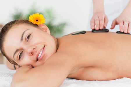 Charming woman having a hot stone massage  in a spa photo