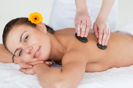 Close up of a cute brunette enjoying a hot stone massage with a flower on her ear photo