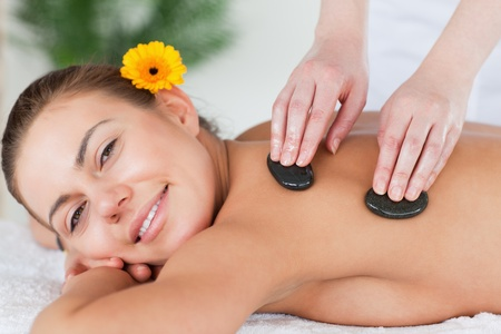 Close up of a smiling woman enjoying a hot stone massage in a spa photo