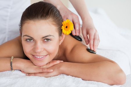 Smiling woman enjoying a hot stone massage with a flower on her ear photo