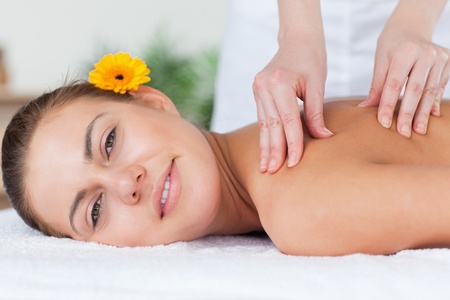 Beautiful woman having a shoulder massage in a spa photo