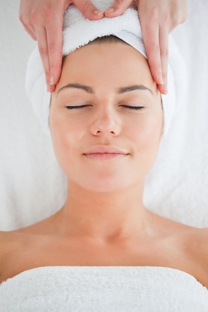 Portrait of a cute woman having a facial massage wearing a towel photo
