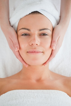 Portrait of a charming brunette having a facial massage wearing a towel photo