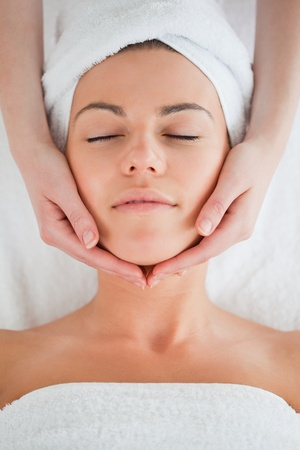 Portrait of a delighted brunette having a facial massage closing her eyes photo