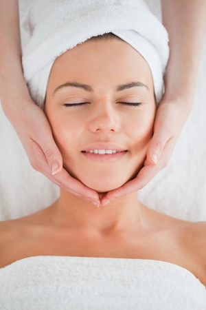 Portrait of a smiling woman having a facial massage closing her eyes photo