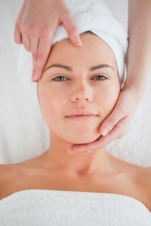 Portrait of a cute woman enjoying a facial massage looking at the camera photo
