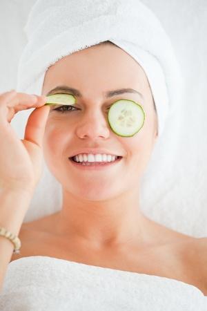 Mujer joven con una sonrisa de complicidad con rodajas de pepino en la cara en un spa