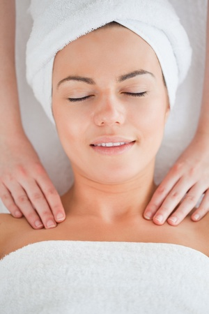 Delighted woman having a shoulder massage wearing a towel photo