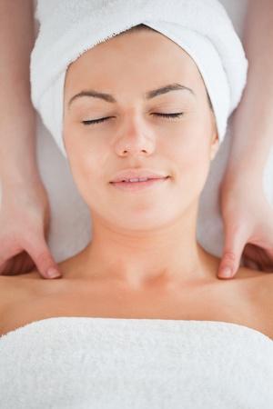 Delighted brunette having a shoulder massage in a spa photo