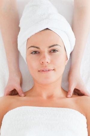 Delighted brunette enjoying a shoulder massage in a spa photo