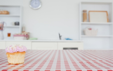 A cupcake on a tablecloth in a kitchen photo