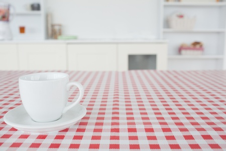 A cup of tea on a tablecloth in a kitchen photo