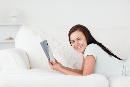 Relaxed woman on a sofa holding a book while looking at the camera photo