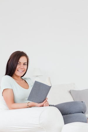 Portrait of a sitting young brunette with a book looking at the camera Stock Photo - 10220983