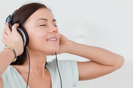 quiet adult: Primo piano di un affascinante bruna ascolto della musica nei confronti di un backgrouond bianco Archivio Fotografico