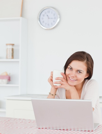 Portrait of a brunette using her laptop and having a tea in her kitchen photo