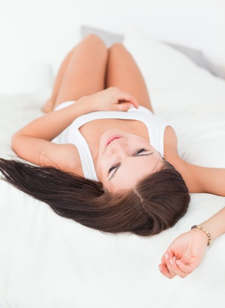 Portrait of a young brunette resting in her bedroom photo