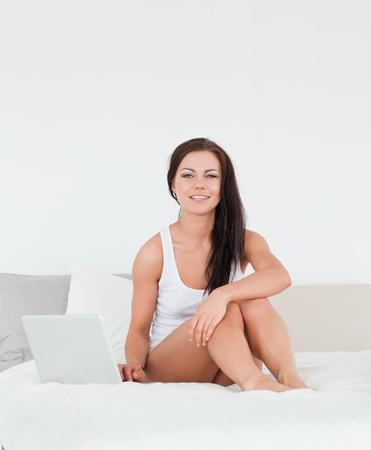Posing brunette with a laptop in a bedroom photo