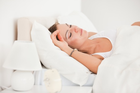 Young brunette sleeping in her bed against a white background photo