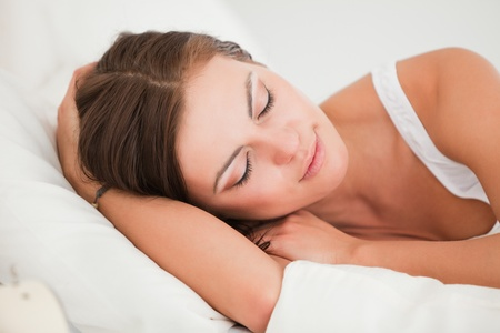 Young woman sleeping in her bed against a white background photo